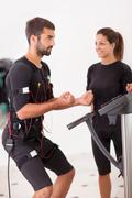 female coach giving man ems electro muscular stimulation exercise - stock photo