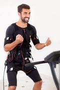 young fit man exercise biceps curl on  electro muscular stimulation machine - stock photo