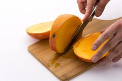 last third of a mango cut off along its fruit pit - stock photo