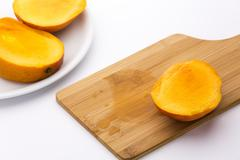 Third of a mango and its juice on wooden board Stock Photos