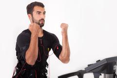 fit man exercise on  electro muscular stimulation machine - stock photo