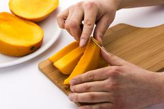peeling away the mango skin from a fruit chip - stock photo