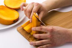 Peeling off the fruit flesh from the mango skin Stock Photos