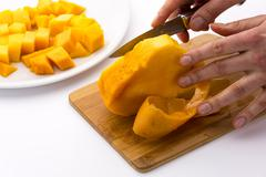 middle third of a mango with its pit being peeled - stock photo