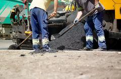Builder on asphalting paver machine during road street repairing works Stock Photos