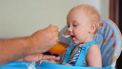 Child, little baby boy kid toddler  eats in the highchair Stock Footage
