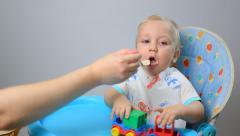 Little baby kid boy eats children's porridge Stock Footage