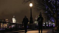 People taking a night time walk, & a woman jogging on a path by the River Thames - stock footage