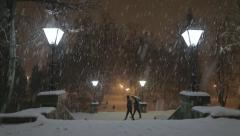 Snow at night in the park with walking people Stock Footage