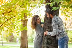 Young couple having fun in autumnal woods, couple peeking from behind a tree Stock Photos