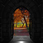 Old arched church doors opening out onto beautiful, colorful forest Stock Photos