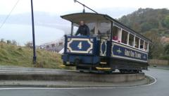 A tram on the Great Orme Tramway climbs a steep hill with a dramatic corner Stock Footage