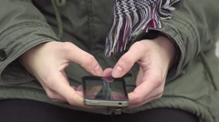 Close up on young woman hands writing text message on her small smart phone Stock Footage