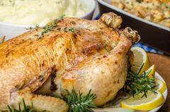feasting - stuffed roast chicken with herbs - stock photo