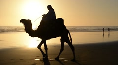 A berber riding a camel during the sunset Stock Footage