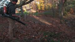 Landscaper begins to blow leaves down a hill Stock Footage
