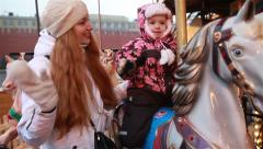 Young charming mom and her daughter ride on the carousel in the winter. Stock Footage
