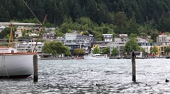 Watercraft and buildings on the waterfront of Queenstown, New Zealand. - stock footage