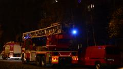 Fire engine (car) in front of building (flats) - urban street with cars - fire Stock Footage