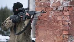 Sniper comes out and makes a shot and hiding behind a wall Stock Footage