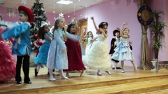 Children in carnival costumes play freeze game on stage at Christmas matinee - stock footage