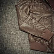 Fashionable leather jacket brown close-up on a dark background - stock photo