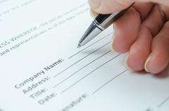 Female hand filling a document with company name Stock Photos