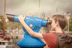 teenage boy with rucksack looking through a sightseeing monocular - stock photo