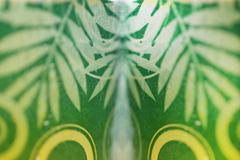 patterned glass of water with green leaves attached. - stock photo