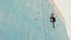 brave child crawling on the climbing wall - stock footage