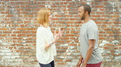 Young couple mess around in front of a brick wall Stock Footage