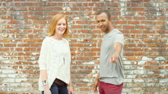 Young couple points into camera and make faces Stock Footage