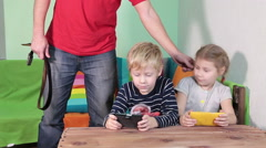Caucasian father with strap in hands trying to grab smartphones from kids hands Stock Footage