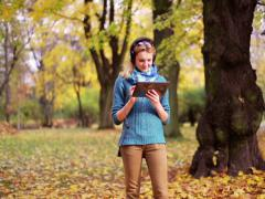 Pretty girl listening music on tablet in the park Stock Footage