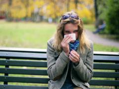 Girl blowing nose and freezing in the park Stock Footage