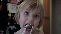 Cute Little Girl Licking Frosting off Beaters in Kitchen Stock Footage