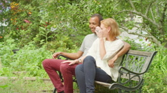 Young couple flirt on a bench, smile into camera Stock Footage
