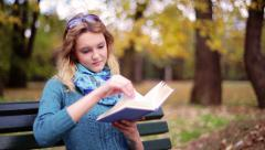 Girl sitting in the park on the bench and reading book Stock Footage