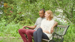 Young couple sit on bench in park and talk Stock Footage