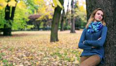 Pensive girl standing in the park and leaning on tree Stock Footage