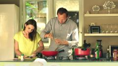 Young couple slicing meat and adding seasoning on pan in kitchen at home HD Stock Footage