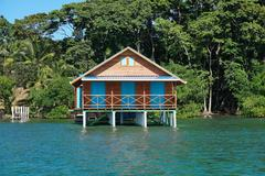 Bungalow over water with tropical vegetation Stock Photos