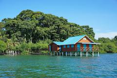Overwater bungalow with lush tropical vegetation Stock Photos