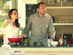 Young couple cooking and tasting prepared sauce in kitchen at home NTSC Stock Footage