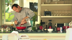 Handsome man cooking and pouring sauce in kitchen at home HD - stock footage