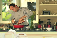 Handsome man cooking and pouring sauce in kitchen at home NTSC - stock footage