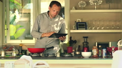 Man with tablet computer cooking and adding seasoning in kitchen at home HD Stock Footage