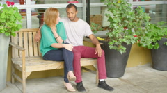 Man with arm around woman chats on a bench Stock Footage