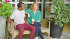 Man puts his arm around woman on a bench sharing coffee Stock Footage
