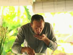 Handsome man tasting disgusting salad in kitchen at home NTSC Stock Footage
